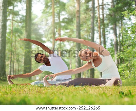 fitness, sport, yoga and people concept - happy couple stretching on mats over green woods background - stock photo