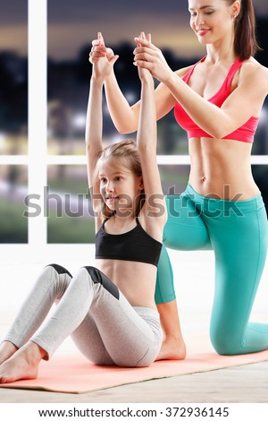 fitness, sport, yoga, and people concept - 10 years old  girl stretching  with personal trainer at fitness class in evening
