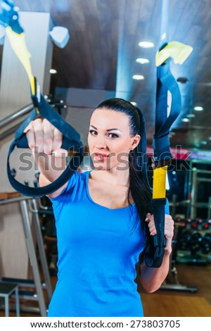 fitness, sports, exercise, technology and people concepts - smiling young woman doing exercise at the gym