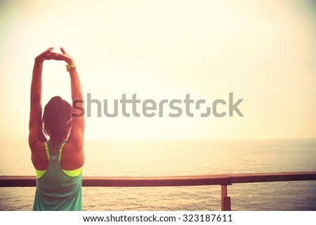 fitness sports woman runner stretching on wooden boardwalk seaside - stock photo