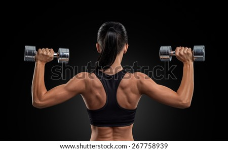 Fitness sporty woman in training pumping up muscles of the back and hands with dumbbells - stock photo