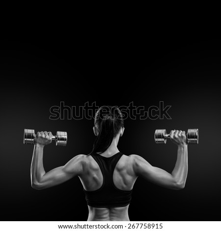 Fitness sporty woman in training pumping up muscles of the back and hands with dumbbells. Black and white concept image - stock photo