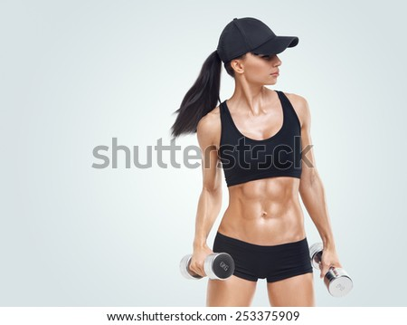 Fitness sporty woman in training pumping up muscles with dumbbells isolated on white background. Strong abs showing. Image with copyspace for text. - stock photo