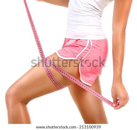 Fitness sporty woman measuring her hip with a measuring tape. Young Beautiful Girl Woman her Leg with a Metric Tape measure. Standing Sideways. Girl measures her thigh Measuring after weight loss. - stock photo
