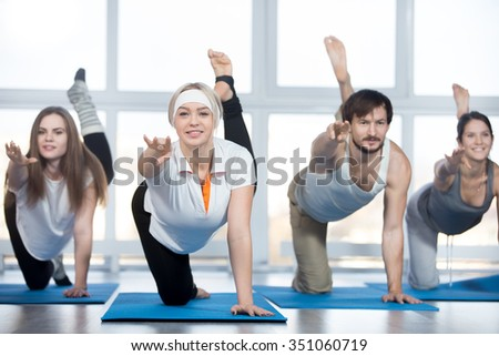 Fitness, stretching practice, group of four beautiful happy fit young people working out in sports club, doing kneeling kickbacks, exercise for lower back, hips and buttocks with instructor in class - stock photo