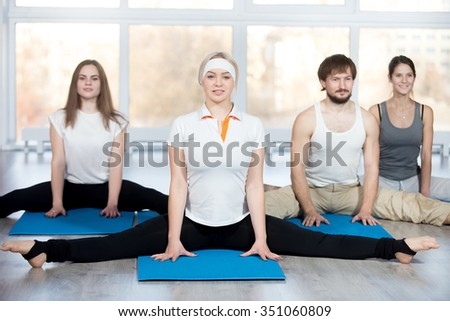 Fitness, stretching practice, group of four beautiful happy fit young people working out in sports club, doing easy variation of Wide-Angle Seated Forward Bend pose on blue mats in class - stock photo