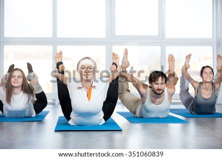 Fitness, stretching practice, group of four beautiful happy fit young people working out in sports club, doing backbend exercise on blue mats in class, full length - stock photo