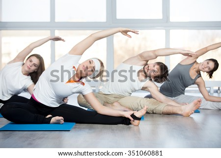 Fitness, stretching practice, group of four beautiful happy fit young people working out in sports club, doing side bend exercise, Revolved Head to Knee pose on blue mats in class - stock photo