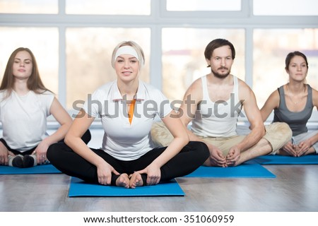 Fitness, stretching practice, group of four beautiful happy fit young people working out in sports club, doing Butterfly Pose for inner thighs, groins, and knees on blue mats in class - stock photo