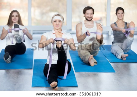 Fitness, stretching practice, group of four beautiful happy fit young people working out in sports club, doing hamstring stretch exercises with props belts on blue mats in class - stock photo