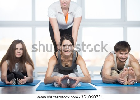 Fitness, stretching practice, group of three beautiful happy fit young people working out in sports club, doing seated forward bend pose on blue mats in class with instructor - stock photo