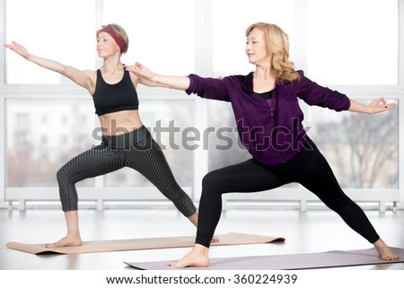 Fitness, stretching practice, group of two attractive happy smiling fit mature women working out in sports club, doing lunge, Warrior II posture, Virabhadrasana 2 pose in class, full length - stock photo