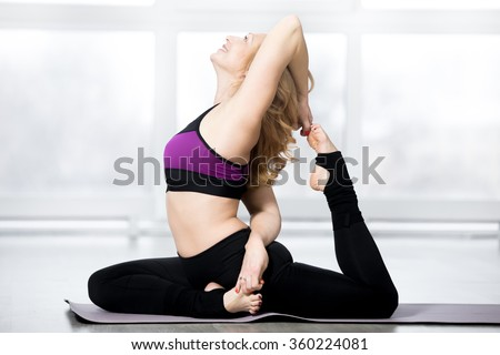Fitness, stretching workout, attractive happy fit mature woman warming up, working out in sports club, doing Eka Pada Rajakapotasana yoga posture, One-legged King Pigeon Pose in class, full length - stock photo