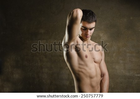 Fitness strong with abdominal fit muscle latin 20s man posing and showing haired armpit - stock photo