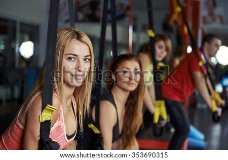 Fitness team doing stretching exercise holding band in the gym. Young active people training arms muscles with elastic rope in sport club.  - stock photo