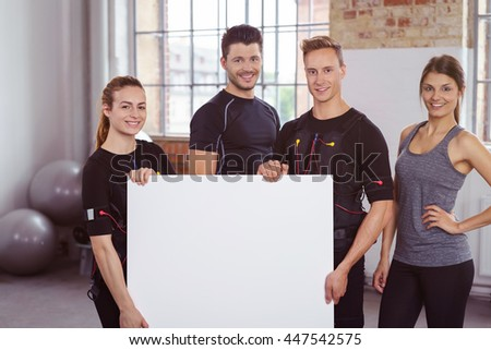 Fitness team in a ems gym with four smiling young people, two men and two women, holding a blank sign with copy space in front of them - stock photo