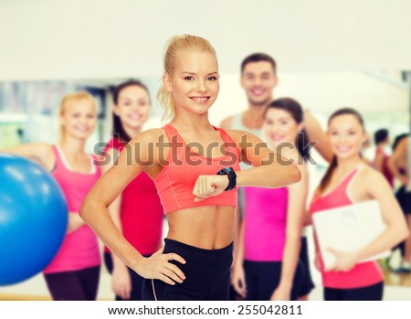 fitness, technology and exercising concept - smiling woman with heart rate monitor on hand - stock photo