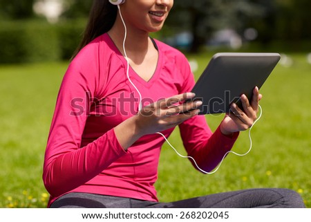 fitness, technology, people and sport concept - close up of smiling african american woman with tablet pc computer sitting on mat outdoors - stock photo