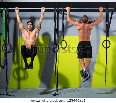 Fitness toes to bar men pull-ups 2 bars workout exercise at gym - stock photo