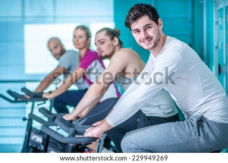 Fitness together on bicycles. Cheerful guy sitting on a stationary bike and looking into the camera. Four friends pedal on a stationary bike at the gym - stock photo