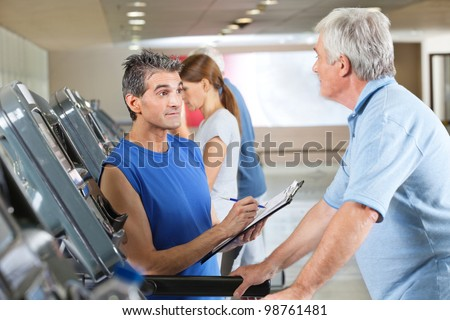 Fitness trainer coaching elderly man on treadmill in gym - stock photo