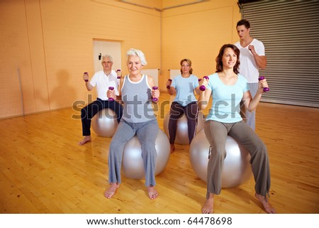 Fitness trainer explaining dumbbell exercises in a gym - stock photo
