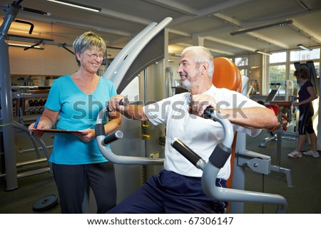 Fitness trainer explaining rowing machine in gym - stock photo