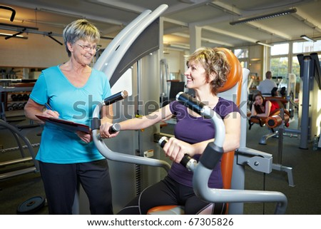 Fitness trainer explaining rowing machine to woman in gym - stock photo
