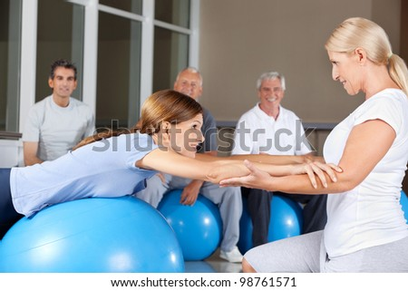 Fitness trainer helping woman doing back exercises in gym