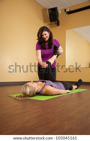 Fitness Trainer Helping Young Woman Stretch