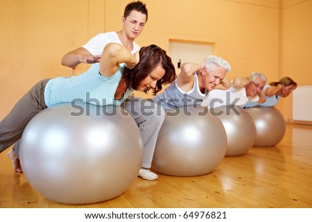 Fitness trainer in a gym teaching back exercises - stock photo