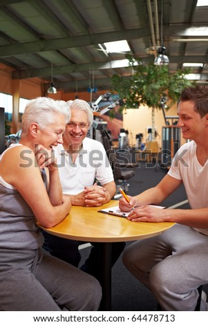 Fitness trainer in gym talking to new customers - stock photo