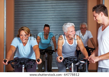 Fitness trainer showing exercises in a gym - stock photo