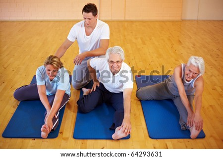 Fitness trainer showing stretching exercises to a group - stock photo