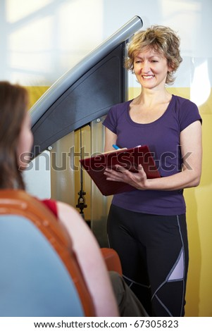 Fitness trainer with clipboard helping woman in gym - stock photo