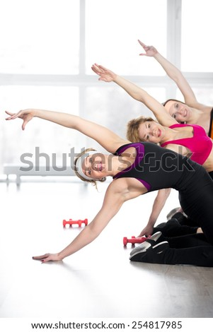 Fitness training, group of three sporty young and mid-aged women doing backbends, exercises for spine, flexibility, weight loss, warming up during sport lesson - stock photo