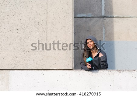 Fitness urban woman taking a workout rest for drinking protein shake. Female motivated athlete holding gym shaker cup. - stock photo