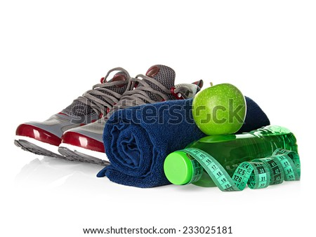 Fitness, weight loss concept with sneakers, green apples, bottle of drinking water and tape measure isolated on white background - stock photo