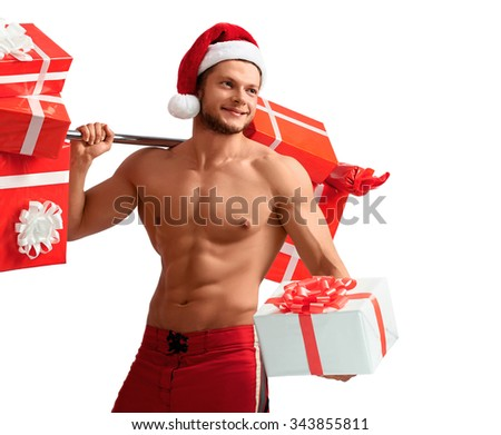 Fitness with Santa. Cropped halflenght studio shot of a young fitness trainer with muscular body wearing Santa Claus hat holding out a gift looking away smiling cheerfully  - stock photo