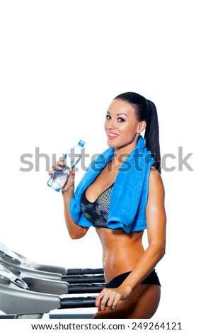 Fitness woman. Beautiful young girl in the gym on the treadmill drinking water. Isolated, white background. - stock photo