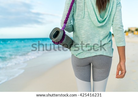 Fitness woman carrying yoga mat with strap on beach going to class training. Closeup of sports equipment, back view of fit athlete in activewear showing fashion leggings and turquoise hoodie. - stock photo