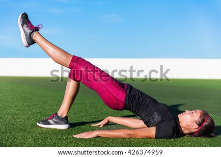 Fitness woman doing bodyweight glute single leg floor bridge lift exercices. Fit Asian woman exercising glutes muscles with one-legged floor bridge butt raise during summer in outdoor gym on grass. - stock photo