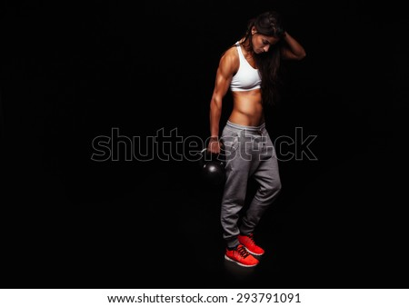 Fitness woman doing crossfit exercising with kettle bell. Fitness instructor on black background. Female model with muscular, fit and slim body. - stock photo