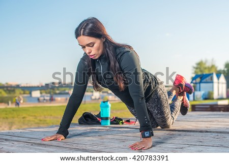Fitness woman doing knee push-ups or press ups exercise outdoors - stock photo