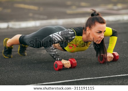 Fitness woman doing push-ups in the stadium, cross training workout. Sporty girl outside - stock photo