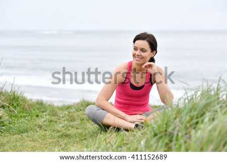 Fitness woman doing relaxation exercises by the sea