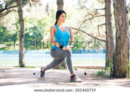Fitness woman doing stretching exercise outdoors in park - stock photo