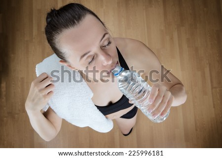 fitness woman drinking water after a workout, view point is high above the model - stock photo