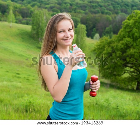 Fitness woman drinking water after workout. Thirsty girl resting taking a break with water bottle drink outside after training.  - stock photo
