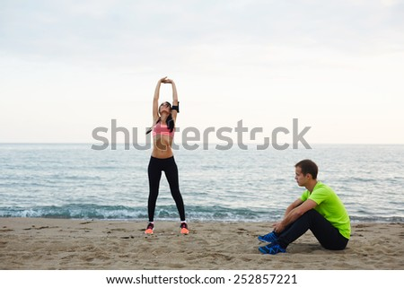 Fitness woman exercising and stretching arms on beautiful beach at evening time, athletic man taking break after workout outdoors looking at her attractive wife exercising, couple engage sport - stock photo